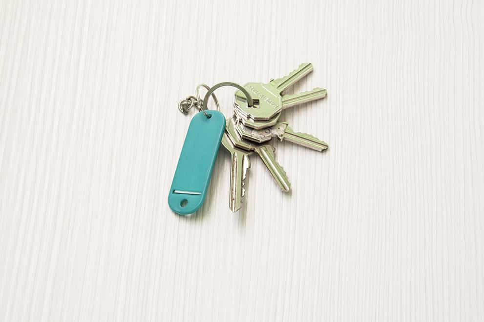 """An image of a set of keys on a white wooden table to represent """"Real Estate Closing Services in Waynesville NC"""" symbolically"""